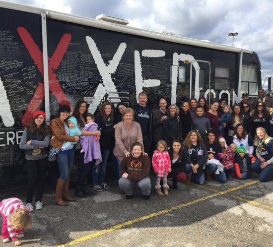 Photo of vaxxed bus with group of people in the front.