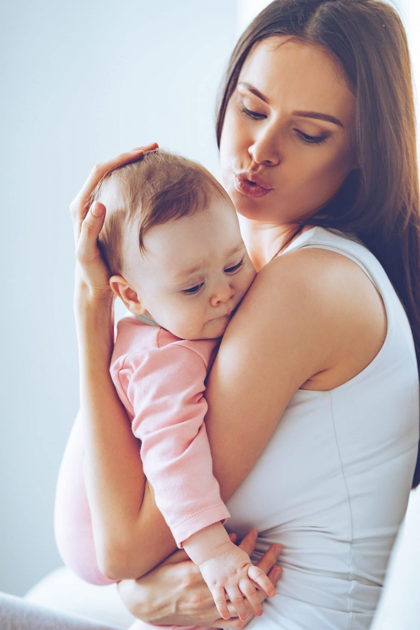 Side view of beautiful young woman calming down her baby girl while holding her in her arms at home